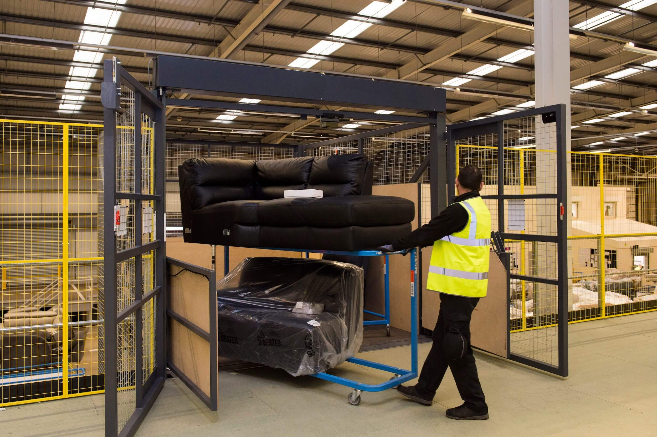 Man removing sofas from goods lift on second floor